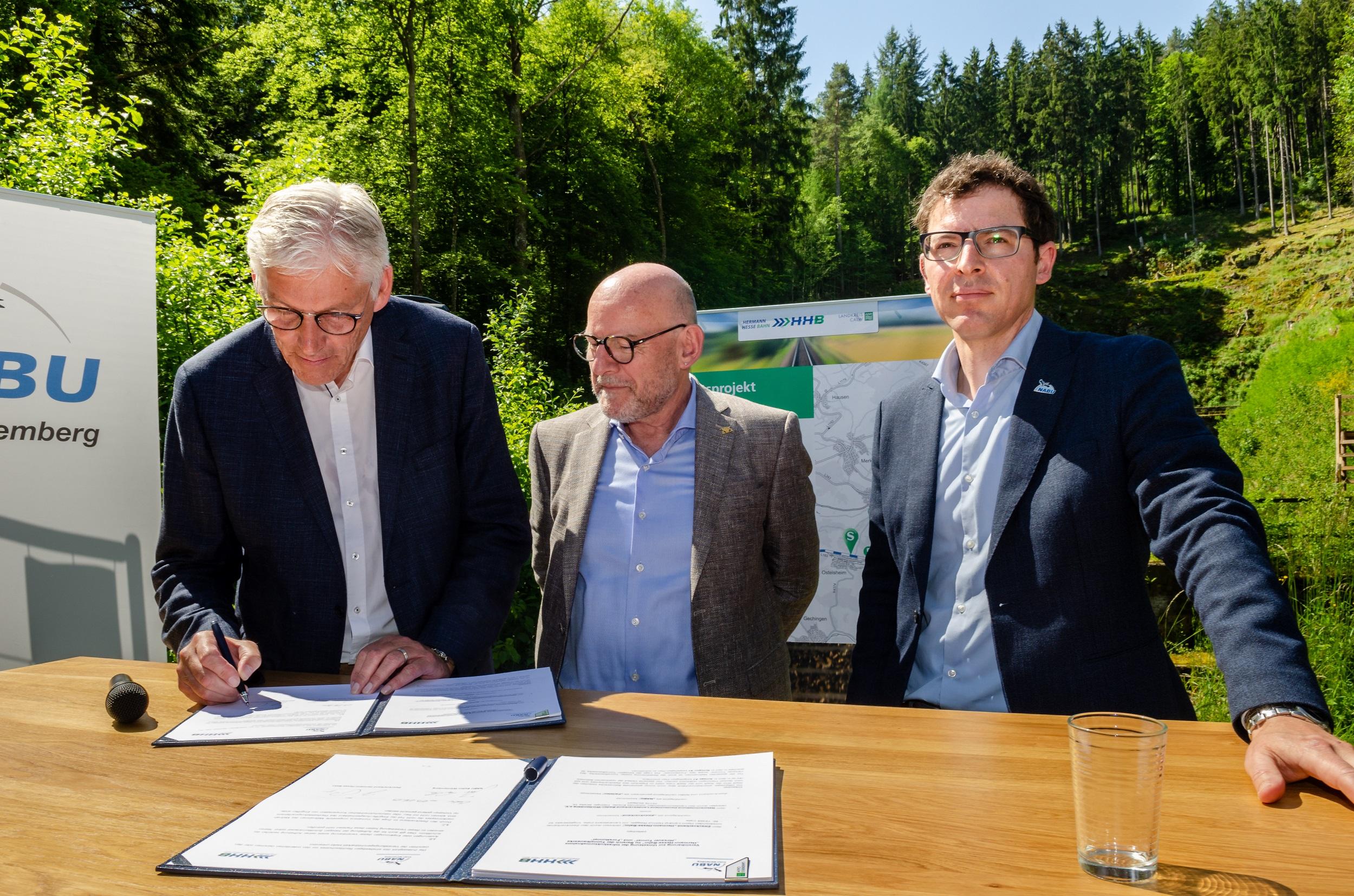 Landrat Helmut Riegger bei der Vertragsunterzeichnung zusammen mit Verkehrsminister Winfried Hermann sowie NABU-Landesvorsitzender Johannes Enssle.